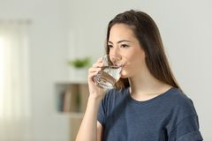 Woman drinking tap water in a glass. Woman drinking tap water in a transparent glass at home royalty free stock images