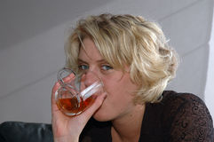 Woman drinking tea. Young blond woman drinking tea from a glass mug Stock Images