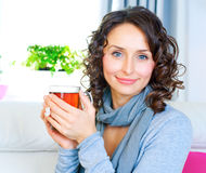 Woman drinking tea. Beautiful Young Woman drinking healthy hot tea Royalty Free Stock Image