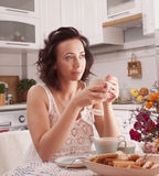 Woman drinking tea. Beautiful girl drinking tea in the morning in the kitchen Stock Images