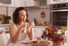 Woman drinking tea. Beautiful girl drinking tea in the morning in the kitchen Royalty Free Stock Photos