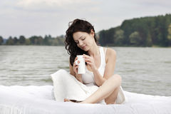 Woman drinking tea on the bed in the sea Stock Photo