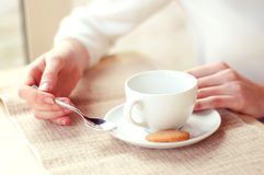 Woman drinking tea in a cafe. Hands closeup. Stock Images