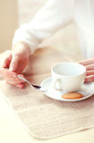 Woman drinking tea in a cafe. Hands closeup. Woman drinking tea with a cookie in a cafe. Hands closeup Royalty Free Stock Image