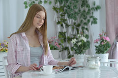 Woman  drinking tea at cafe and reading magazine Stock Images