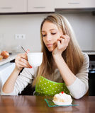 Woman drinking tea with cake   in  kitchen Royalty Free Stock Photography
