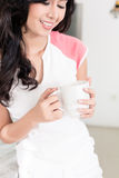 Woman drinking tea or coffee in her Asian kitchen Royalty Free Stock Photos