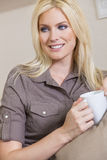 Woman Drinking Tea or Coffee At Home. A beautiful young blond woman drinking tea or coffee from a white mug sitting at home on a her sofa Stock Photos
