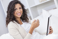 Woman Drinking Tea or Coffee Using Tablet Computer. Beautiful young Latina Hispanic woman smiling, relaxing and drinking a cup of coffee or tea using tablet Royalty Free Stock Photo