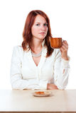 Woman drinking tea with cup on. Beautiful woman sitting behind a table and drinking tea with cup on the side. On white background stock photography