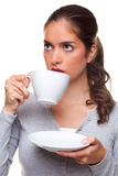 Woman drinking tea from a cup and saucer. A woman drinking tea from a cup and saucer as she is thinking about something, white background Stock Image