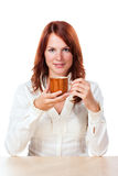 Woman drinking tea with cup under. Beautiful woman sitting behind a table and drinking tea, the cup is lower. On white background stock photos