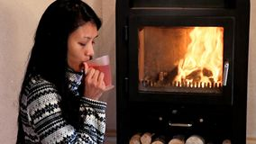 Woman drinking tea by the fire stock video footage