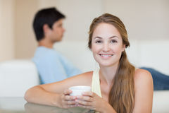 Woman drinking tea while her fiance is sitting on a couch Royalty Free Stock Images