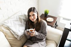 Woman Drinking Tea At Home. Happy Latin woman enjoying winter season with hot and refreshing tea royalty free stock image