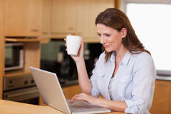 Woman drinking tea while on laptop Royalty Free Stock Photo