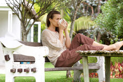 Woman drinking tea outside in backyard Royalty Free Stock Images