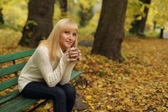 The woman drinking tea in park in the autumn. The women drinking tea on a bench in park in the fall Stock Photography