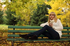 The woman drinking tea in park in the autumn. The women drinking tea on a bench in park in the fall Royalty Free Stock Image