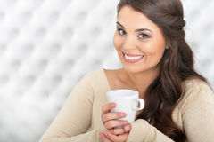 Woman drinking tea. Portrait of a woman drinking tea in light room Stock Images