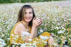 Woman drinking tea from a thermos flask. The young beautiful woman drinks tea from a thermos flask in the field of camomiles Stock Photos