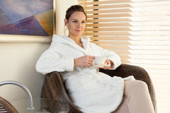 Woman drinking tea in waiting room at spa center Stock Photo