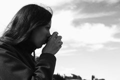 Woman is drinking tea on the waterfront. Young brunette on a journey. Bw. stock photos