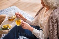 Woman drinking tea. Sitting on the floor near Christmas tree stock photo