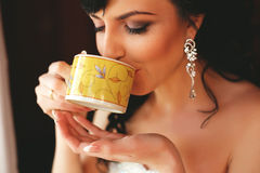 Woman drinking tea from yellow cup Stock Image