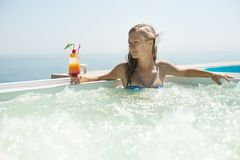 Woman drinking tropical cocktail. At  beach resort Royalty Free Stock Images