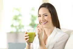 Woman drinking a vegetable juice looking at camera Stock Photography