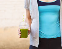 Woman drinking vegetable smoothie after fitness running workout Stock Images