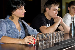 Woman drinking vodka at the bar. With shot glasses lined up in a row in front of her staring thoughtfully at the line up stock image