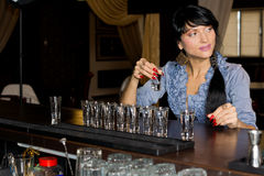 Woman drinking vodka shots at a bar. Attractive young woman drinking vodka shots at a bar sitting with a long line of shot glasses i front of her as she downs royalty free stock photos