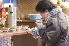 A woman drinking a warm drink. An elderly woman while drinking a hot drink in a traditional Hong Kong street Stock Image