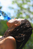 Woman drinking water. Young woman drinking water outdoors. She has a thirst.  Side view Royalty Free Stock Images