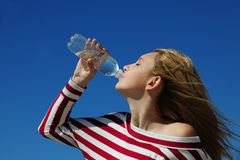 Woman drinking water. Against blue sky stock photo