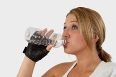 Woman drinking water. Head and shoulders of an attractive young blond woman in workout attire holding and drinking from a water bottle with a glove on hand stock images