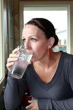 Woman drinking water. Woman drinks tall glass of ice water while looking out the window Royalty Free Stock Photography