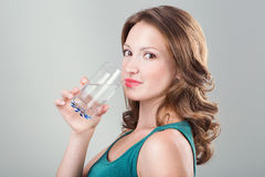 Woman drinking water. Young woman holding glass of water  on grey background. Studio shot Stock Images