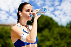 Woman drinking water. Thirsty sporty woman drinking water after training stock photo