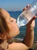 Woman drinking water. Young woman drinking water at the beach under the hot sunlight Royalty Free Stock Photos