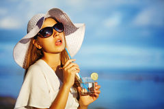 Woman drinking water on a beach Stock Photos