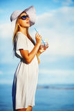 Woman drinking water on a beach Royalty Free Stock Photo