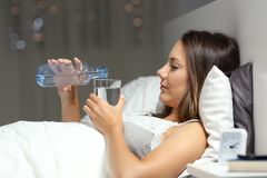 Woman drinking water on the bed in the night Stock Images