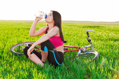 Woman drinking water after biking Stock Photo