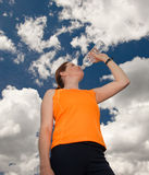 Woman drinking from water bottle. Athletic woman in orange shirt drinking from water bottle with sky and clouds Royalty Free Stock Images