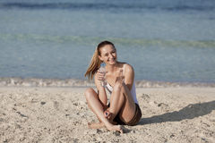 Woman drinking water from a bottle on the beach portrait Royalty Free Stock Photography