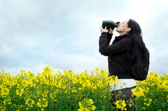 Woman drinking from water bottle in field Stock Photos