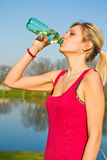 A woman drinking water from bottle after fitness sport exercise Stock Photos